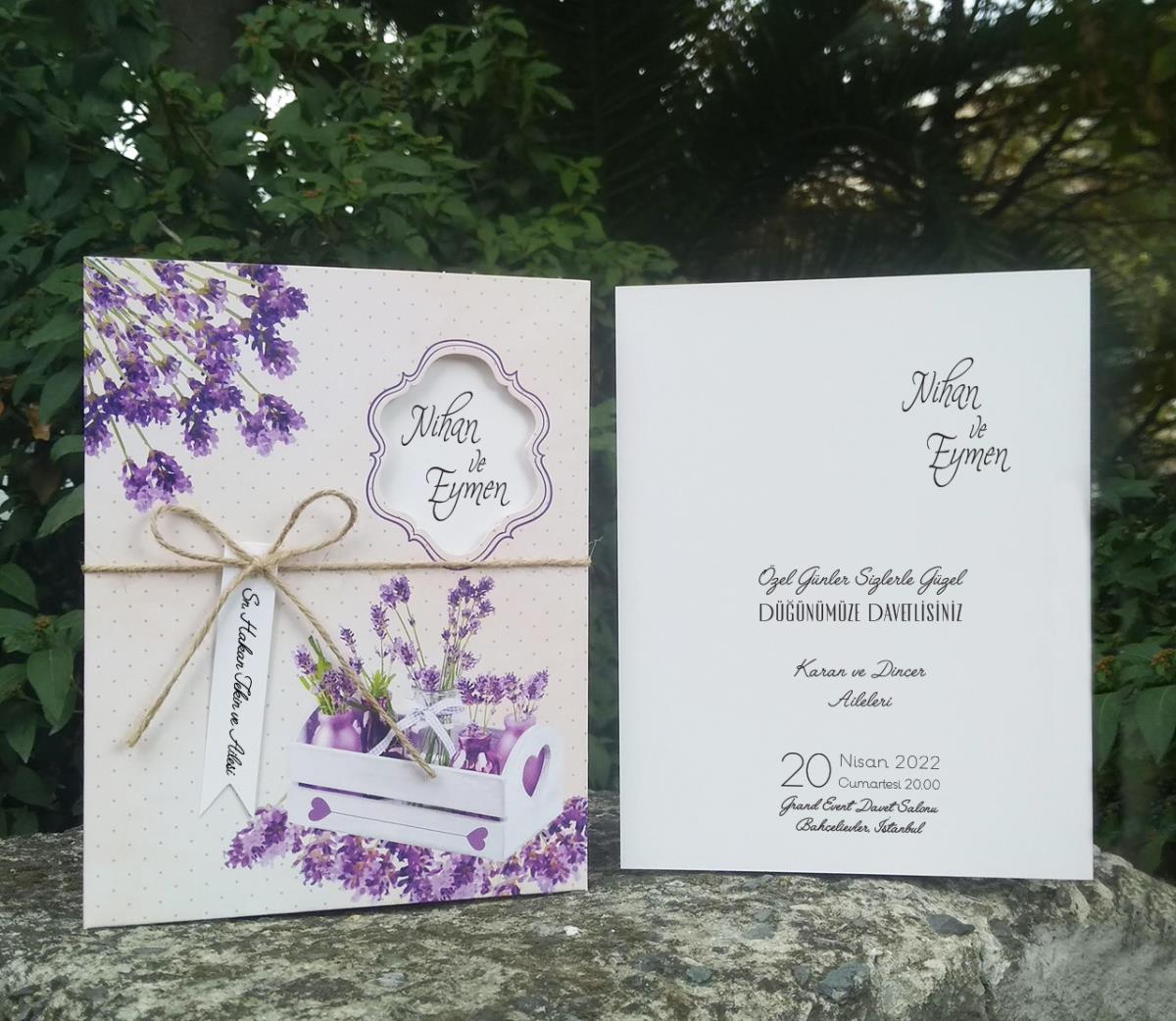 Ahşap saksıda mor lavanta çiçekleri, pudra pembesi zemin üzerinde uygulanmış düğün davetiyesi.