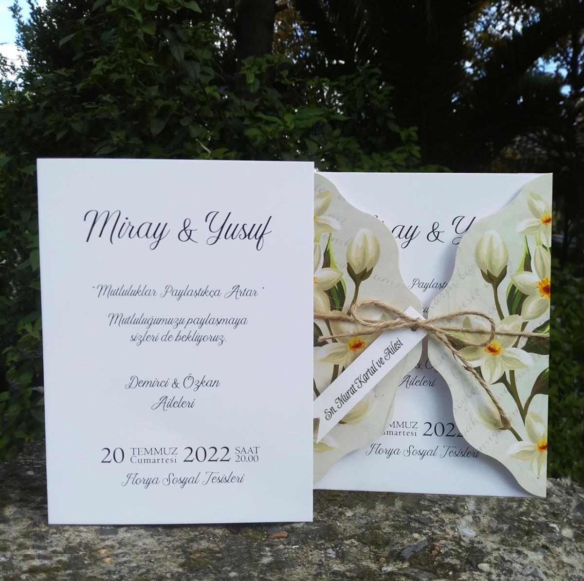 Özel kesimli kapağı zambak motifi ile süslenmiş, kraft iç kartlı düğün davetiyesi ham ip ve isimlik aksesuarlıdır.